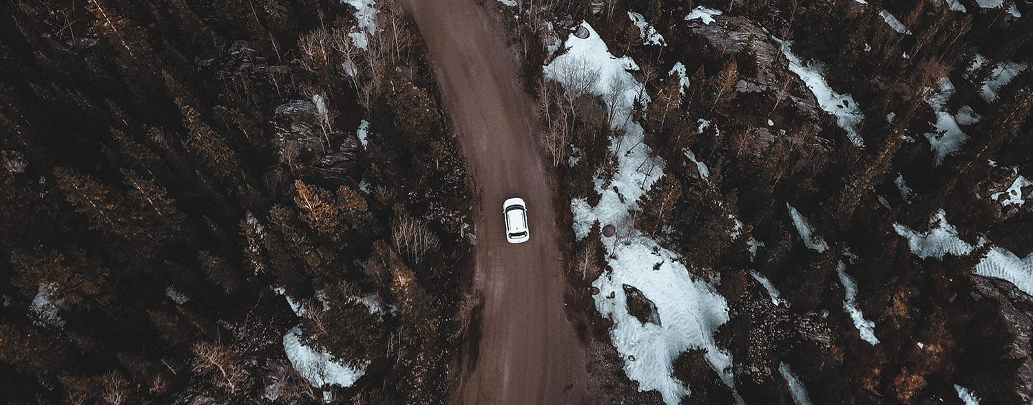 drone shot of car driving through winding snowy mountain pass