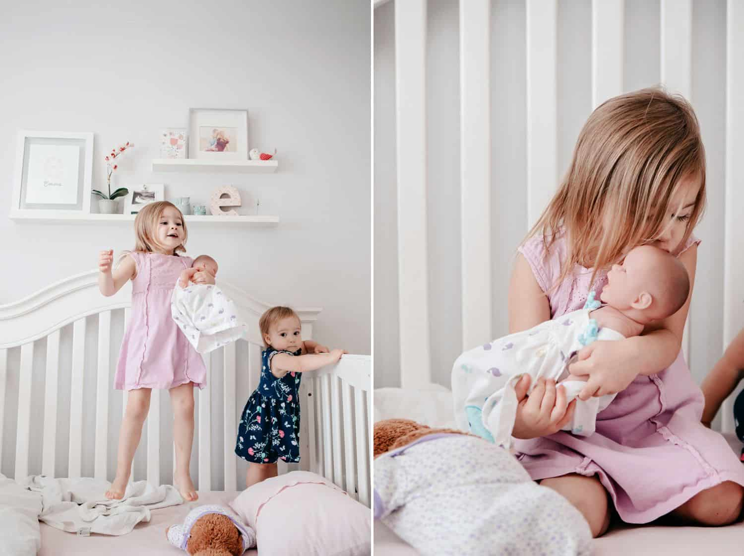 Sisters play in their baby sibling's crib with a doll.
