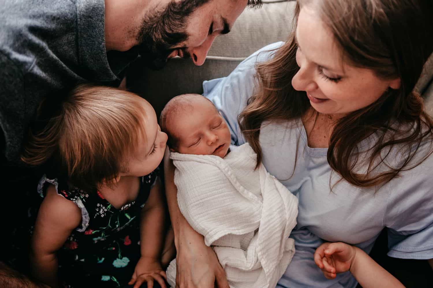 The Ultimate Portfolio Review Tool: A family gathers around their newborn baby.