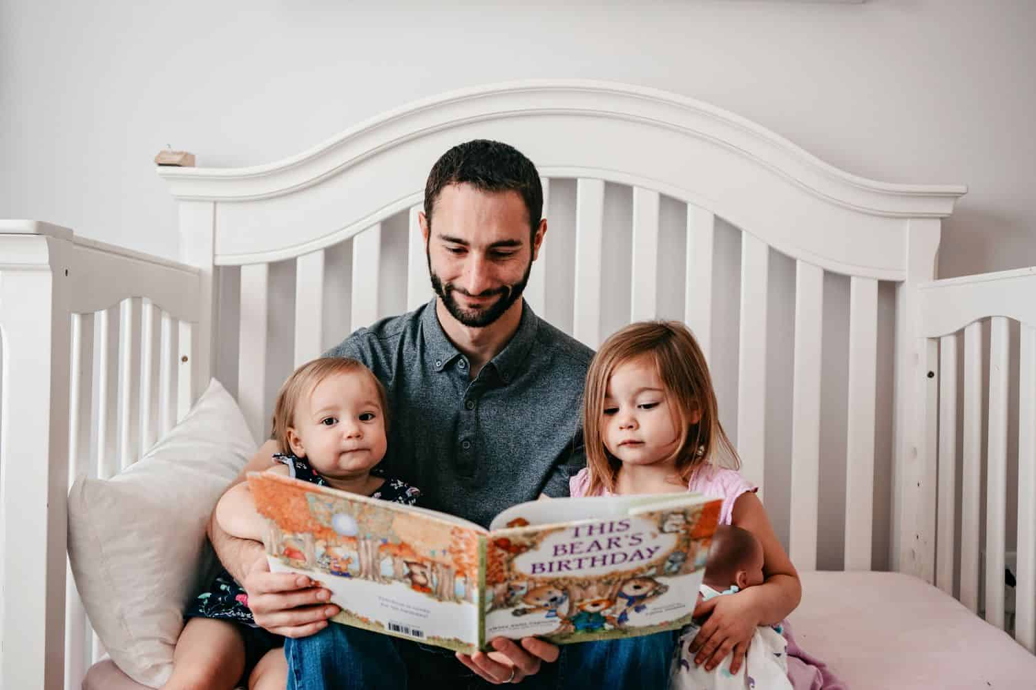 Dad reads a book to his two little daughters.