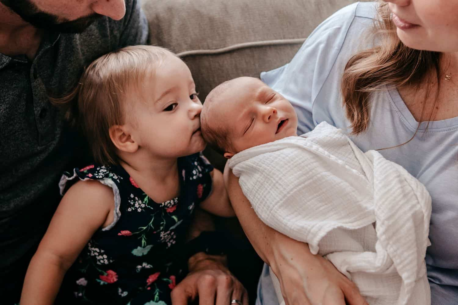 Mom holds a newborn baby so his sister can kiss him on the head.