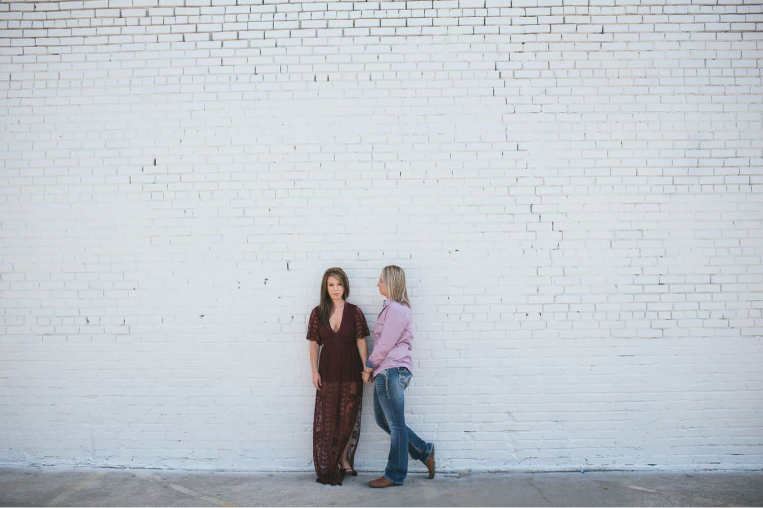 female couple hold hands and stand close against a white brick wall
