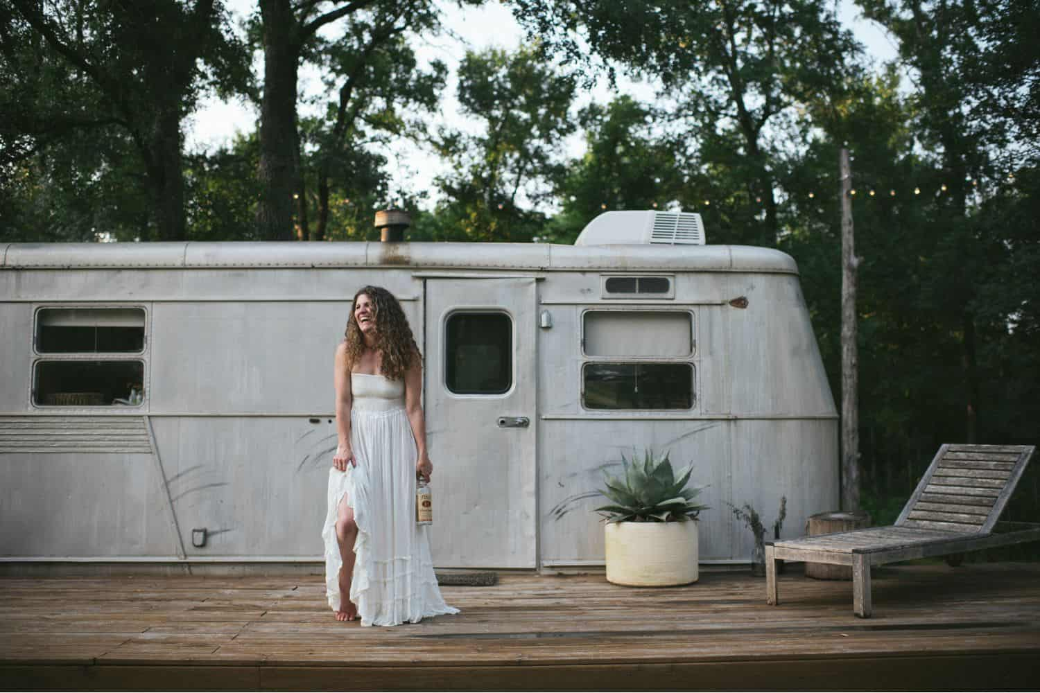 woman in white dress standing in front of a camper