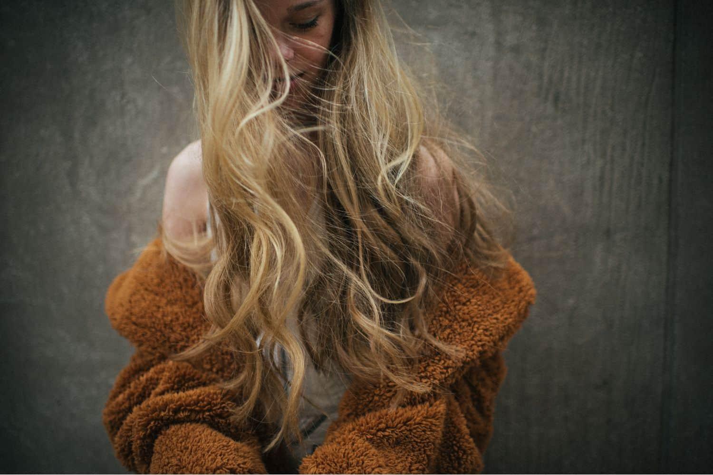 blonde hair waving in the wind, orange coat