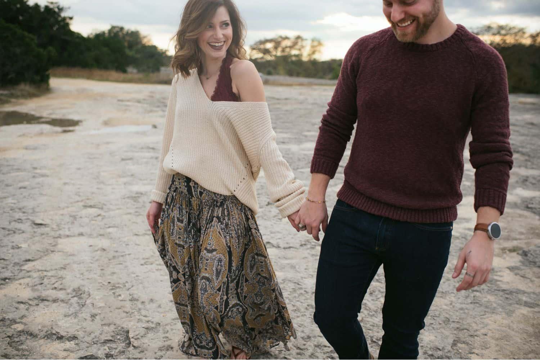 boho couple strolls hand in hand through a desert