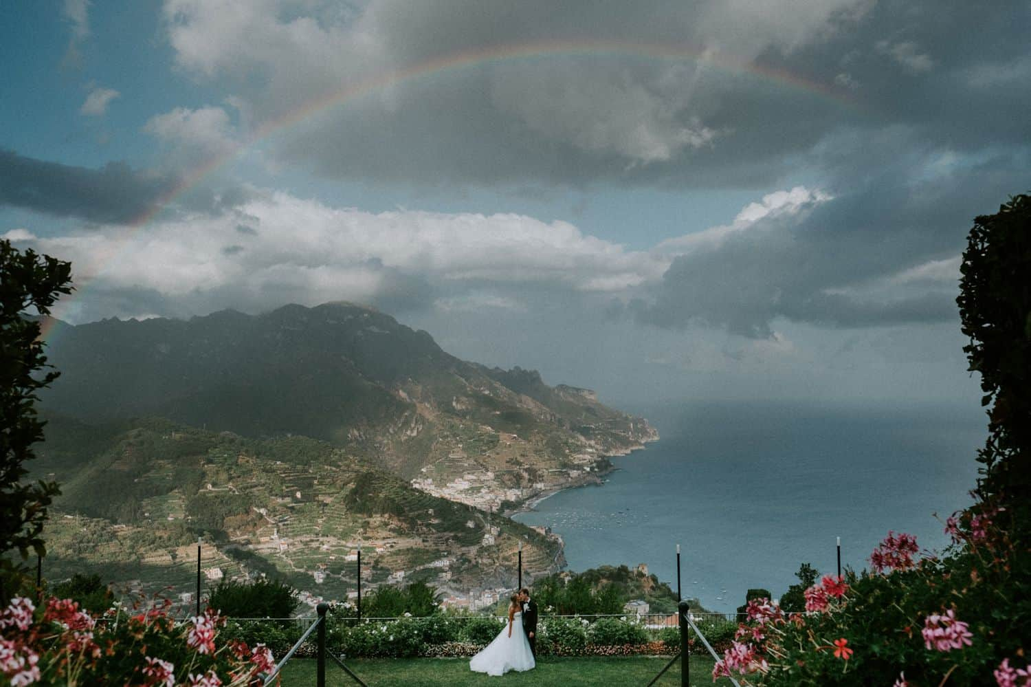 Van Middleton: Bride and groom stand under a seaside rainbow.