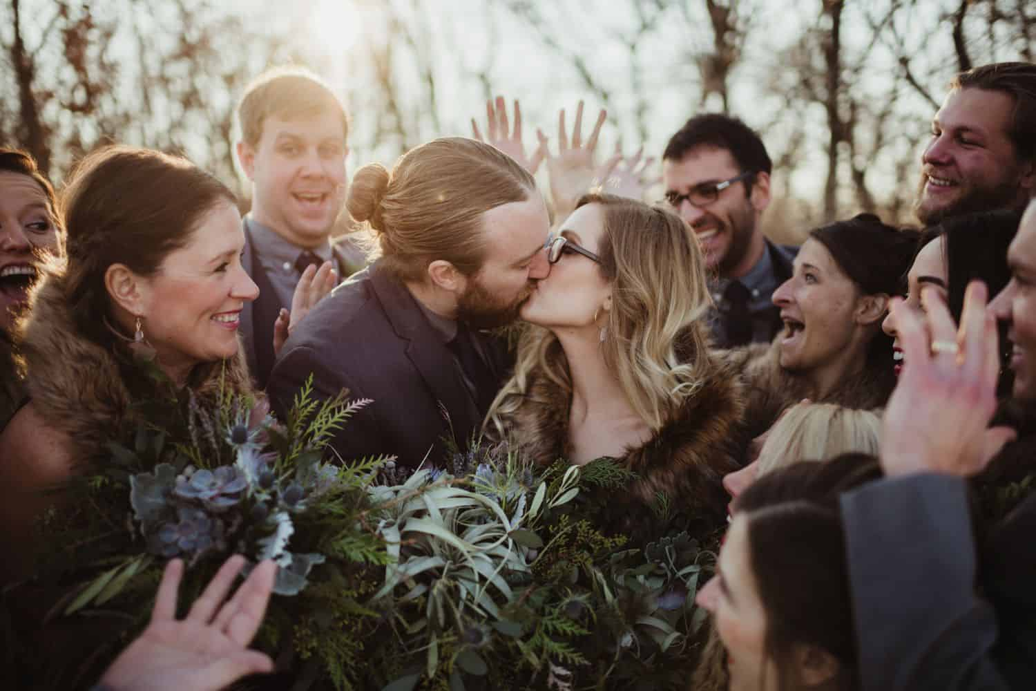 bride in a fur stole kisses her new husband while the wedding party cheers around them