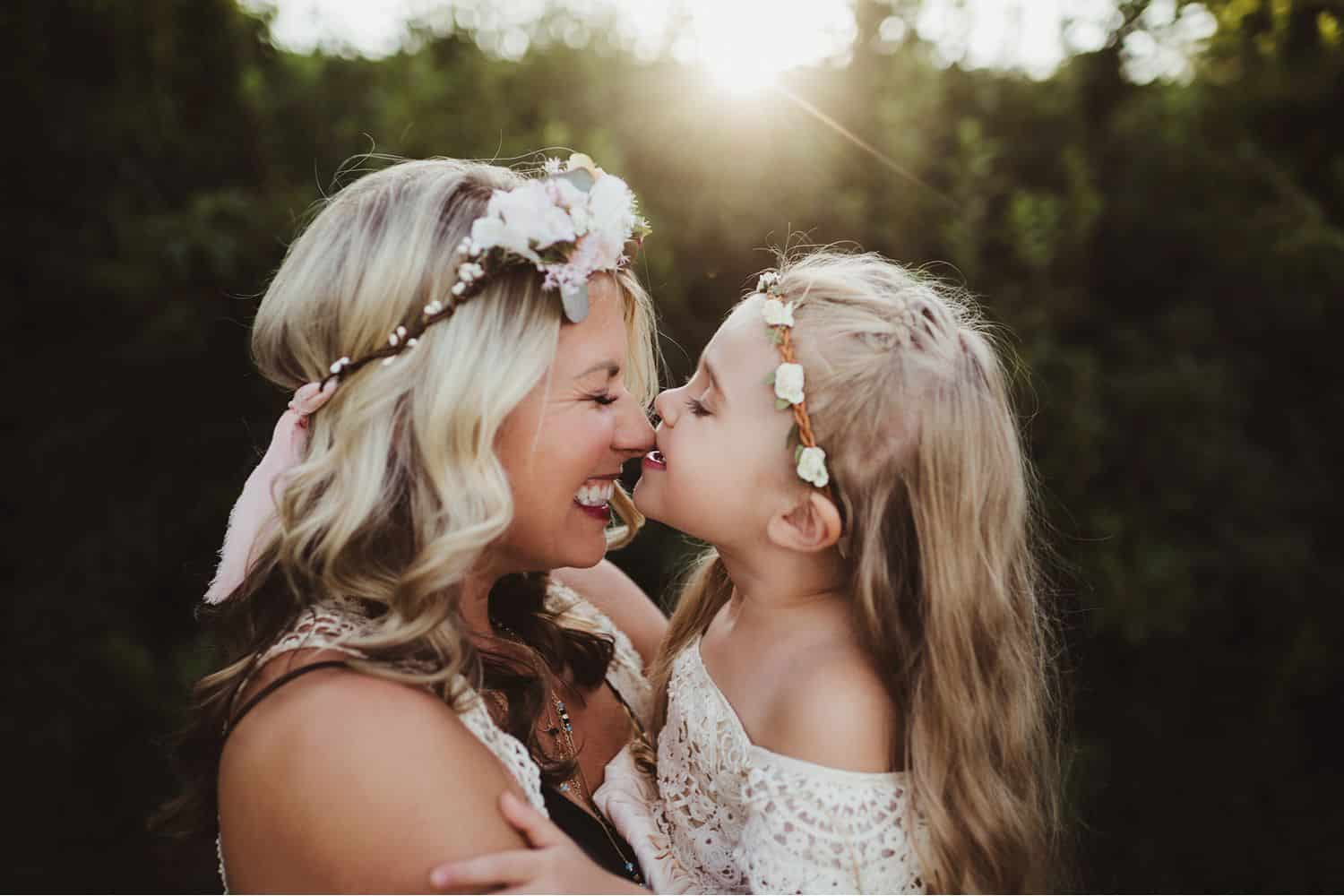 mother and daughter rub noses wearing white lace dresses