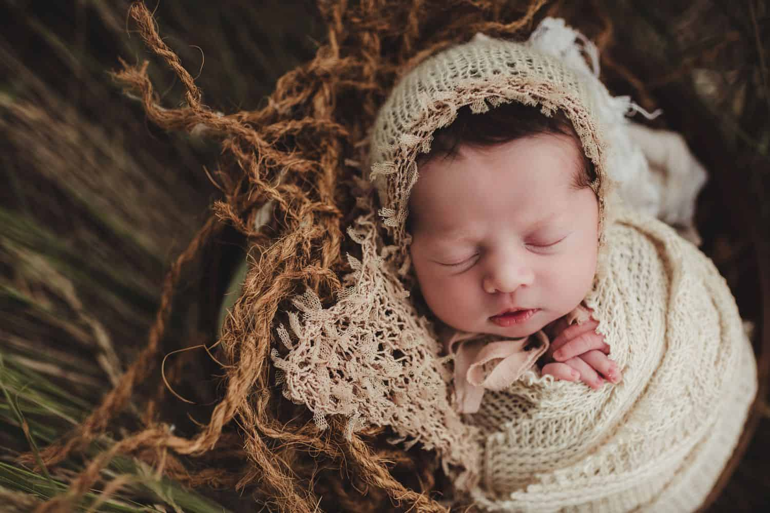 newborn wrapped in burlap and lying in a bed of reeds