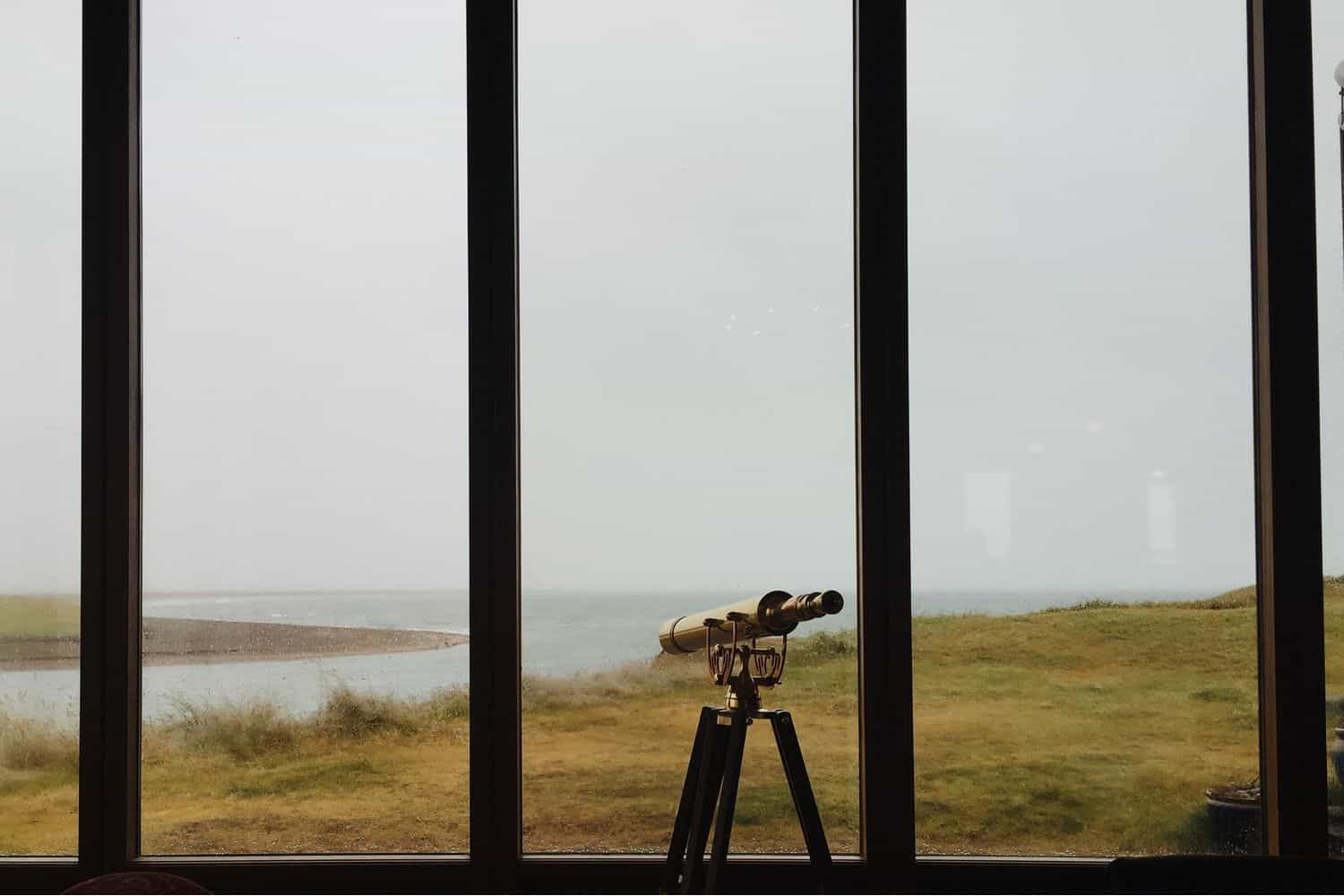 telescope looking through a window over the sea