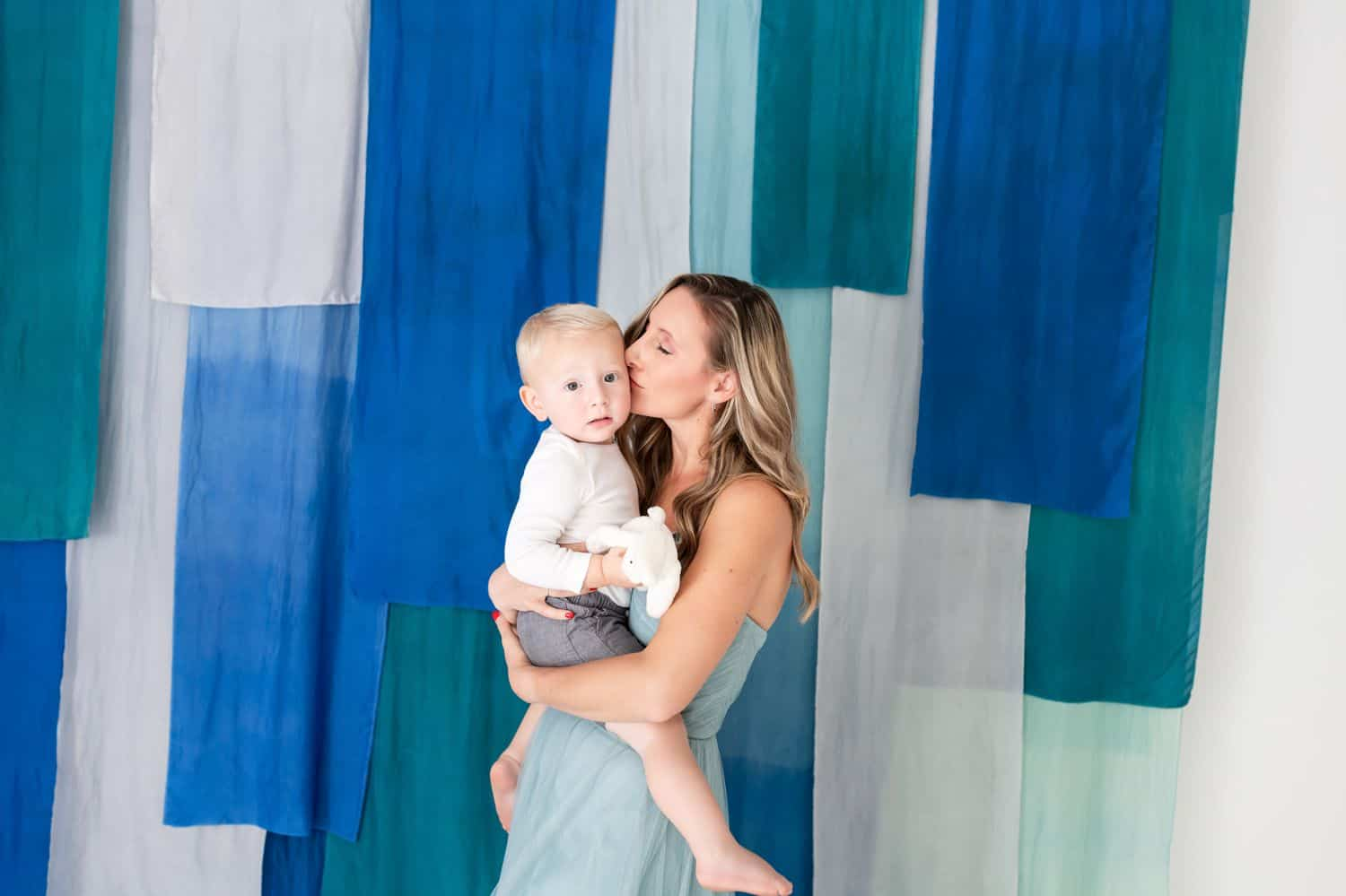 A mom kisses her toddler son on the cheek in front of a blue-draped wall.
