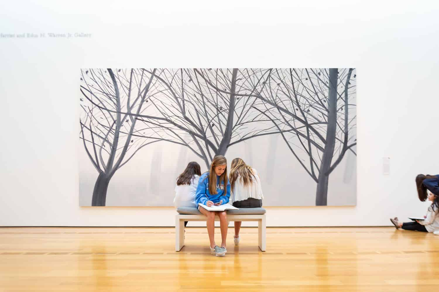 Build Your Dream Photography Business on a Budget: Three schoolgirls sit on a bench in front of a massive gallery painting