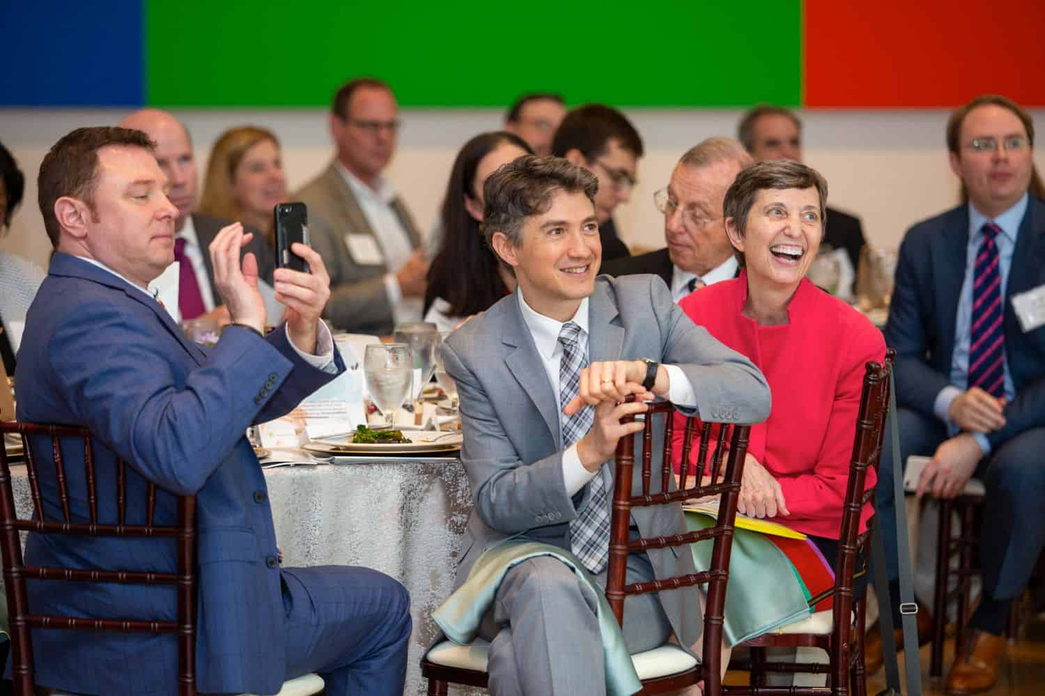 Build Your Dream Photography Business on a Budget: Dinner guests at a corporate event watch a speaker and smile