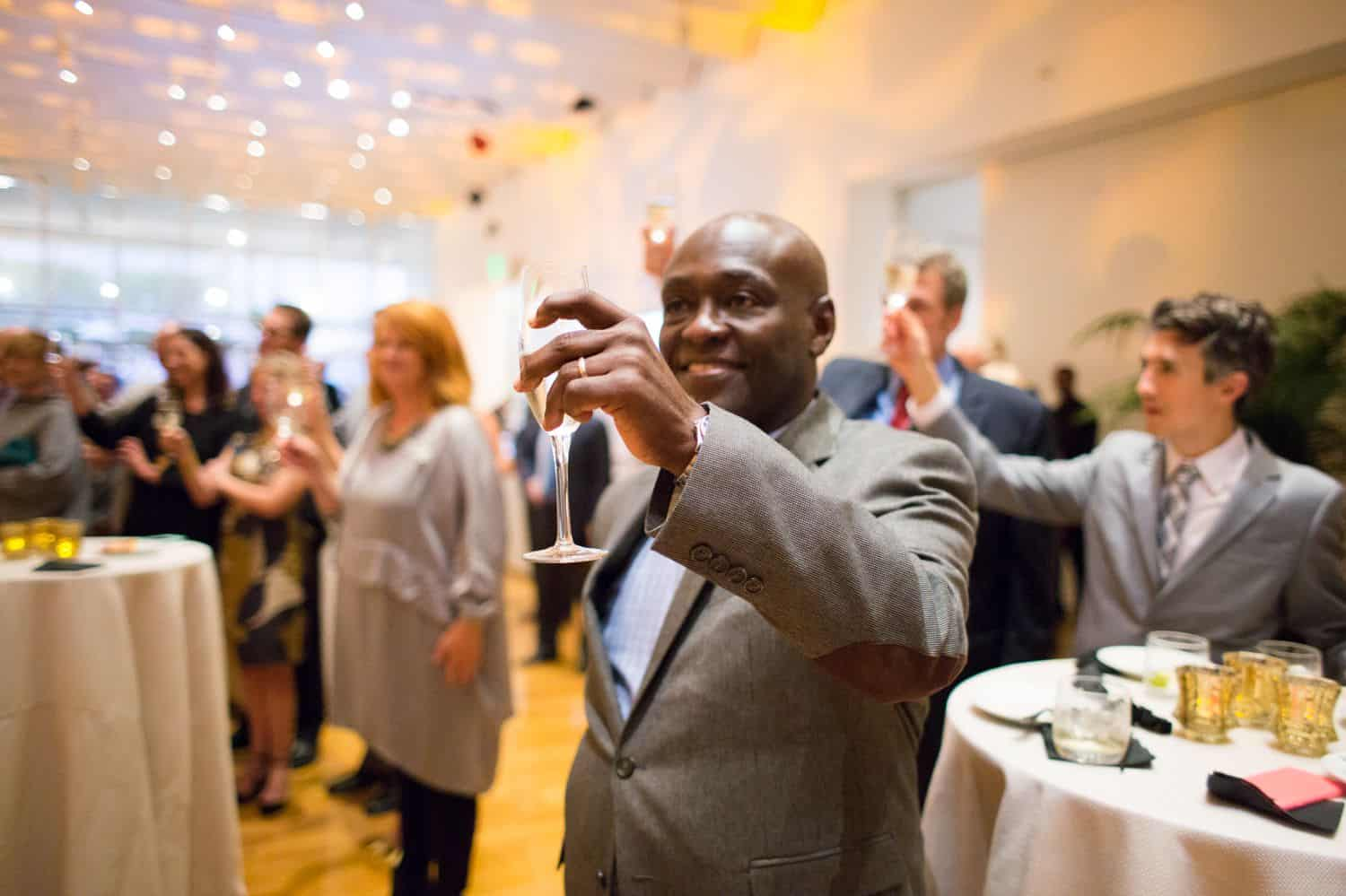 Build Your Dream Photography Business on a Budget: Man gives champagne toast at business event