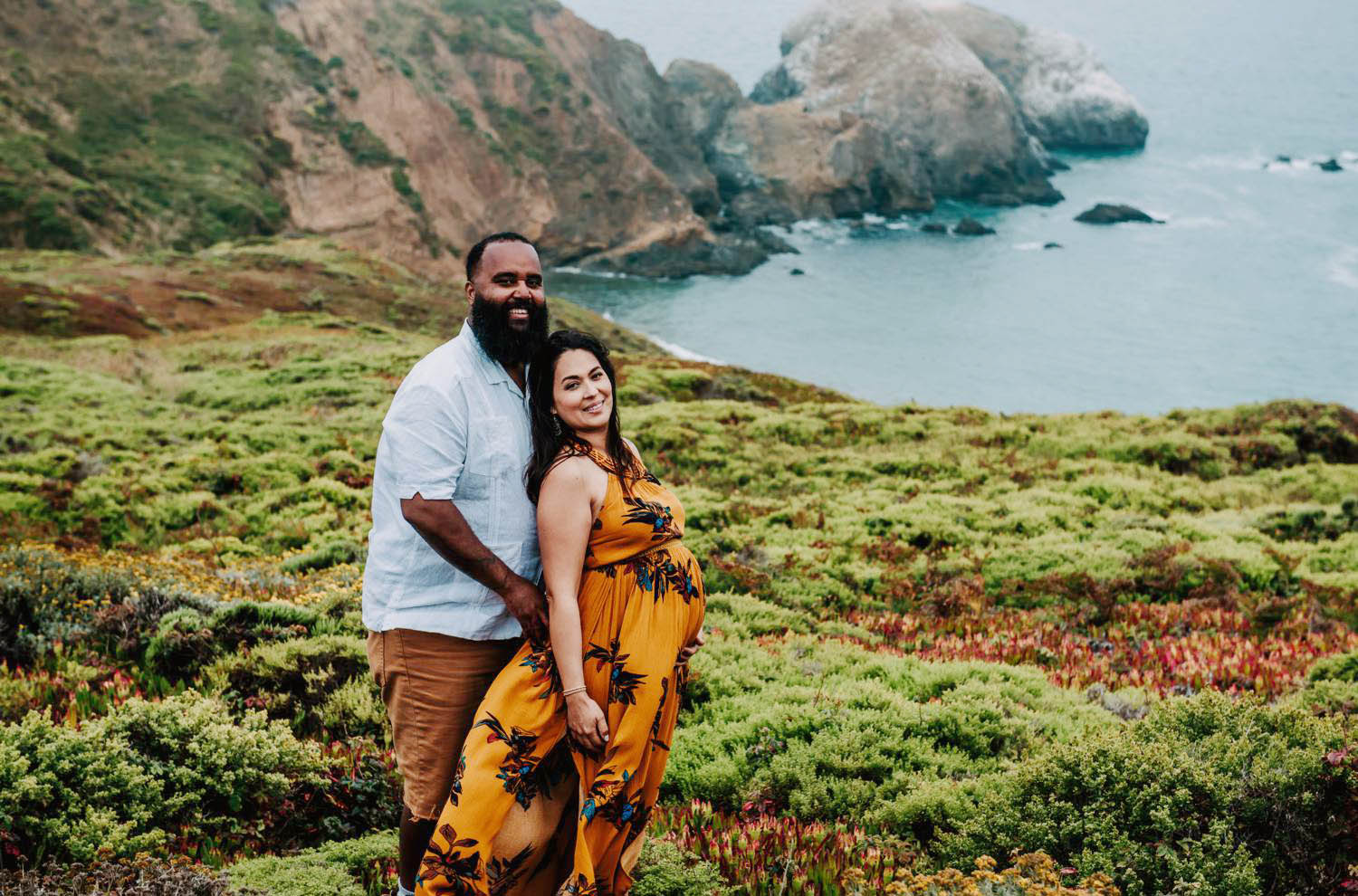 Captured Happiness Photography captures beautiful maternity poses in Hawaii, including this portrait of a man and his pregnant partner standing by the ocean with cliffs behind them.