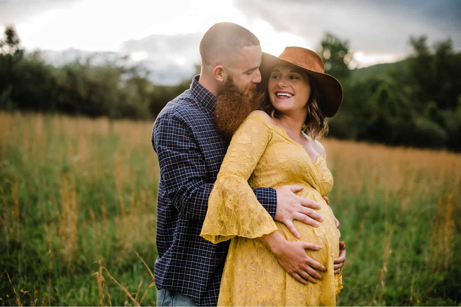 Maternity Poses: man with a plaid shirt and beard pulls his wife close, cradling her belly. She is wearing a brown felt hat and a yellow lace dress.