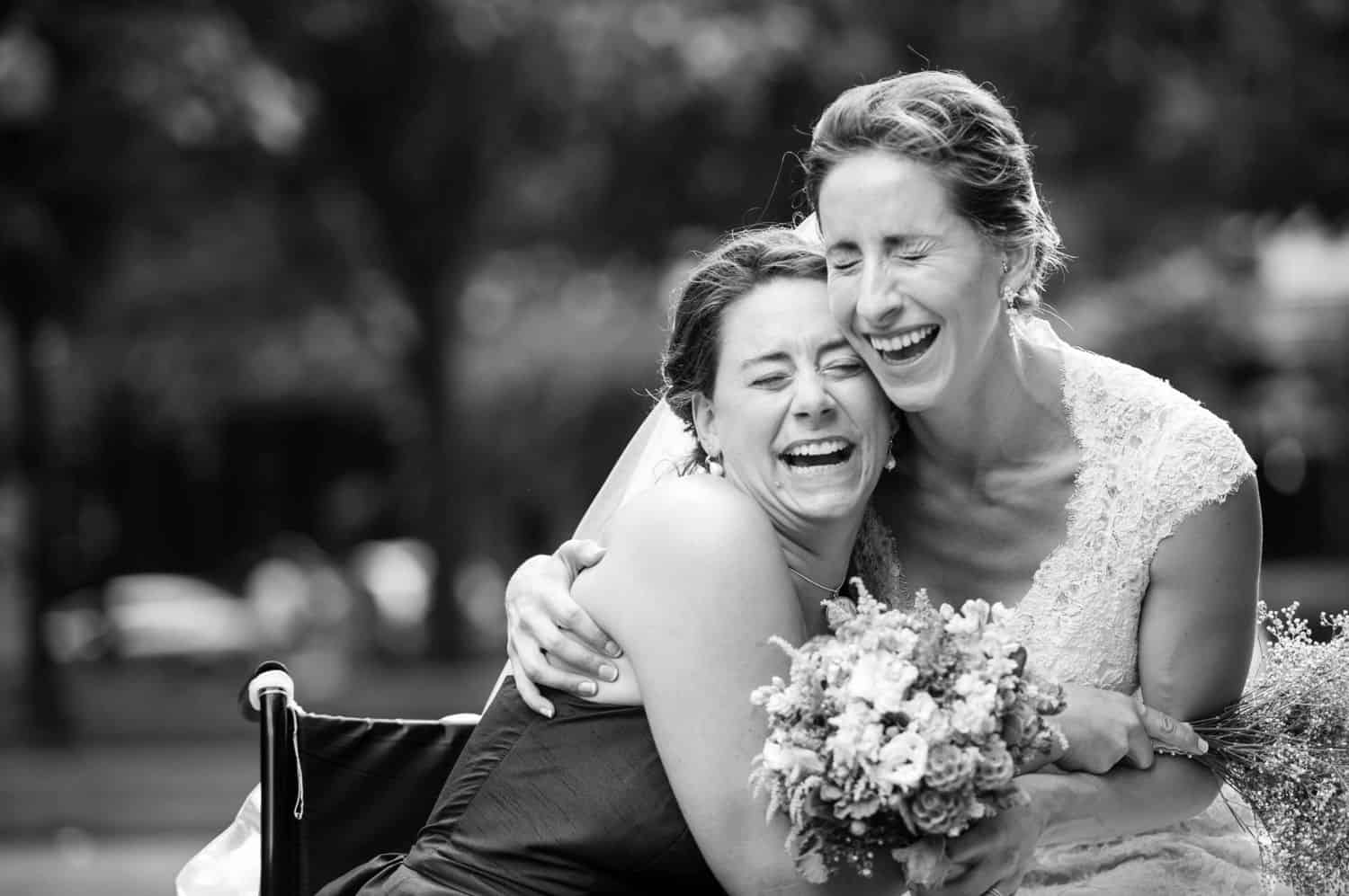 Make Money with Photography: A bride and her bridesmaid hug and laugh