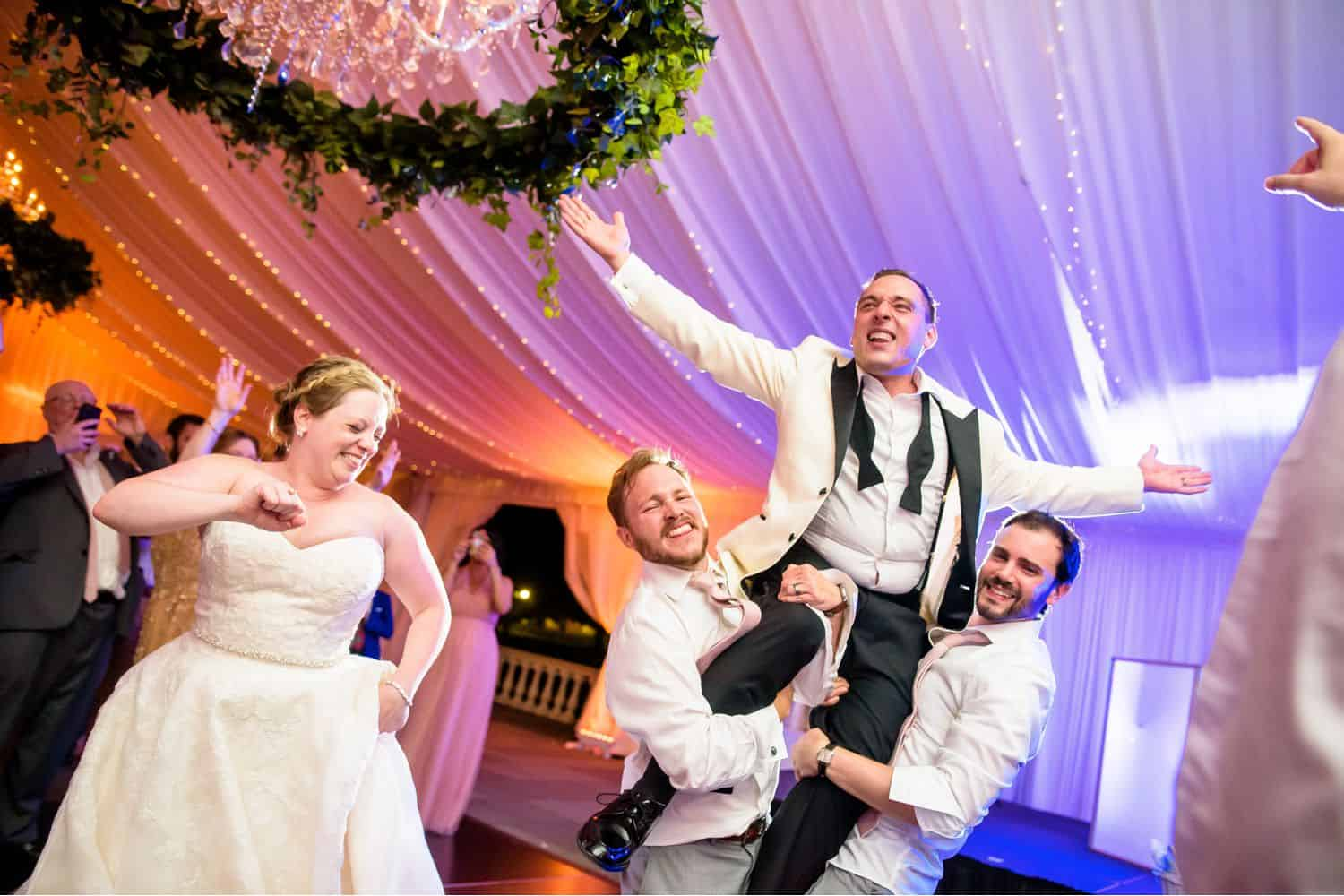 Make Money with Photography: Bride dances while two wedding guests lift Groom into the air.