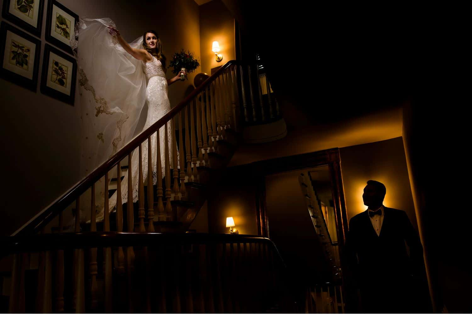 Make Money with Photography: bride stands on stairs with veil flowing while groom stands below illuminated from behind