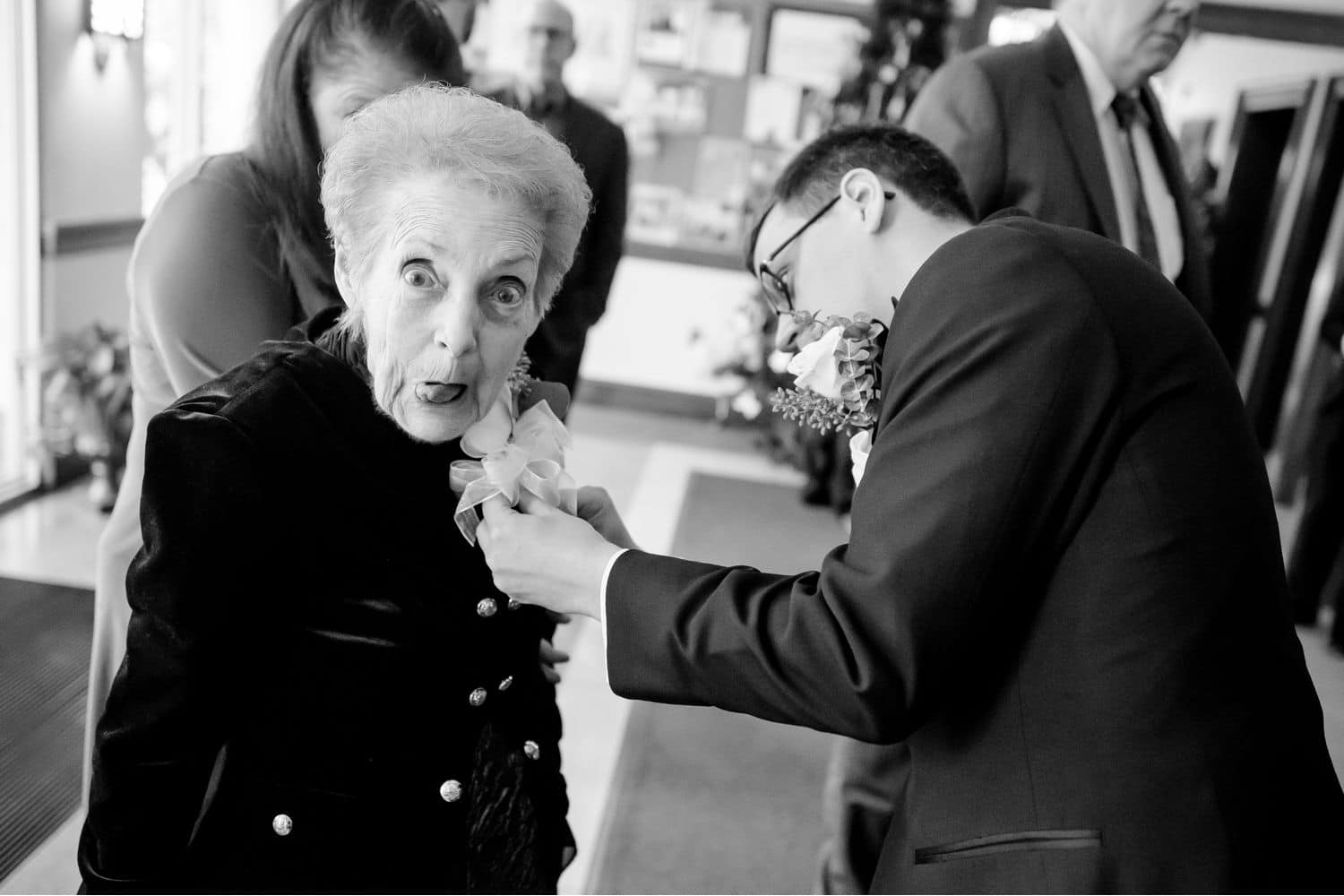 Make Money with Photography: Groom pins a boutonniere on his grandmother as she makes a silly face