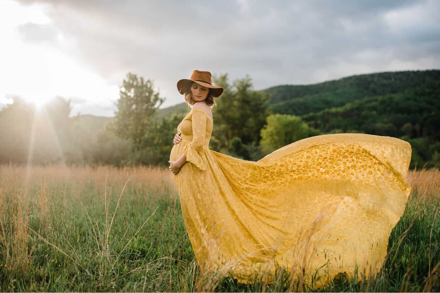 Maternity Poses: Full-length portrait of a pregnant woman in a yellow lace dress wearing a brown felt hat in an overgrown field. Her dress is flowing behind her and she is cradling her belly.