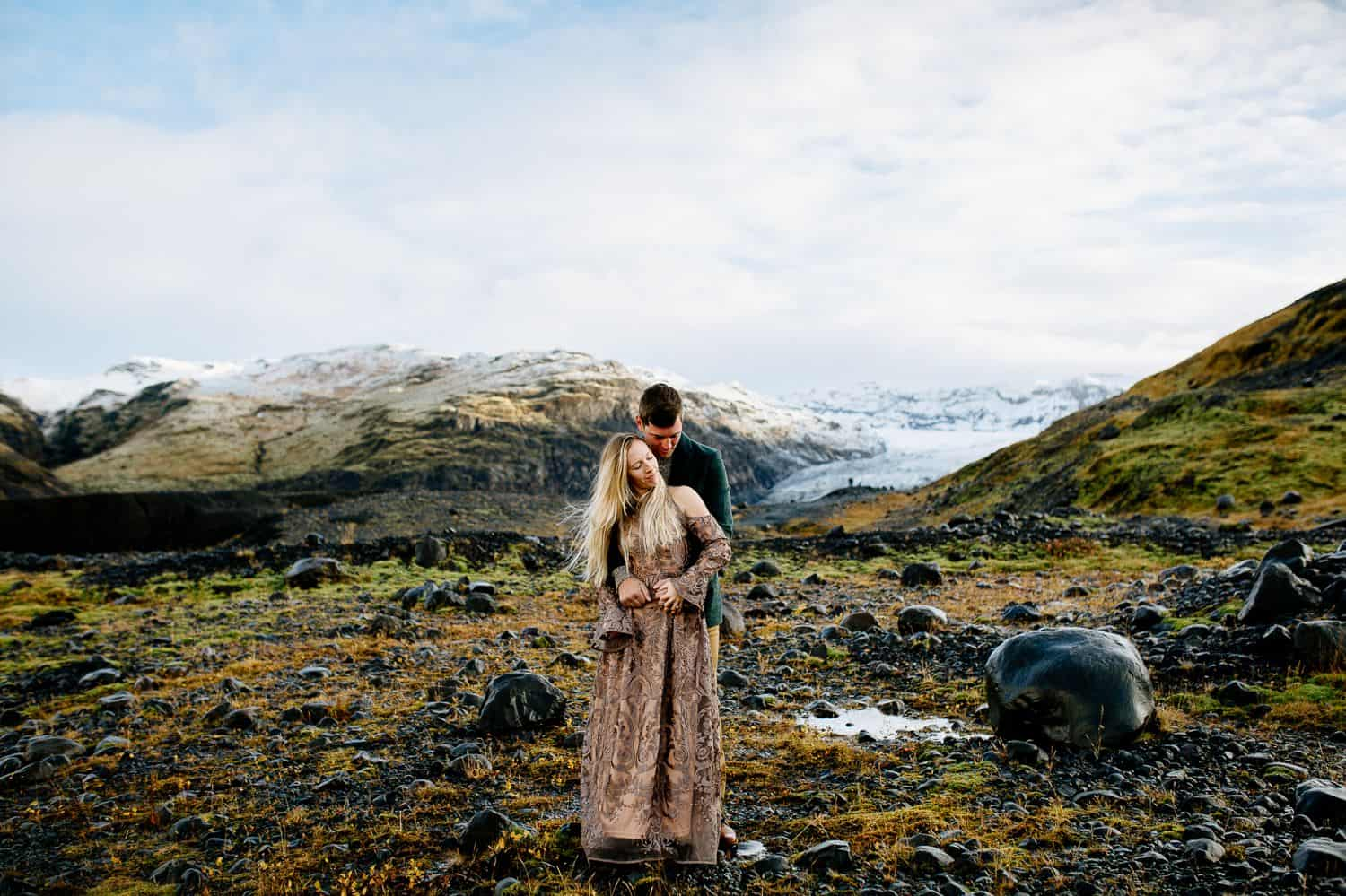 Man in a green jacket embraces a woman in a brown lace dress from behind. In the background you see the green and snow-capped hills of Iceland.