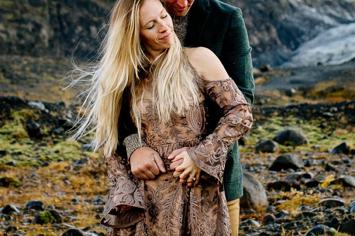 Woman in a brown lace dress is embraced from behind by a man in a green velvet jacket. Only the woman's face is shown.