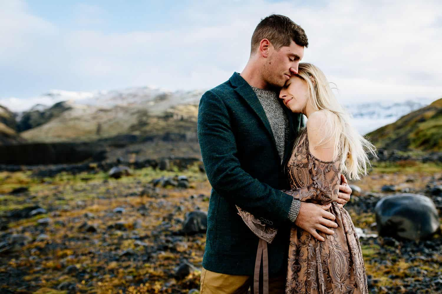 Man in a green jacket embraced a woman in a brown lace dress as they stand in the Icelandic landscape.