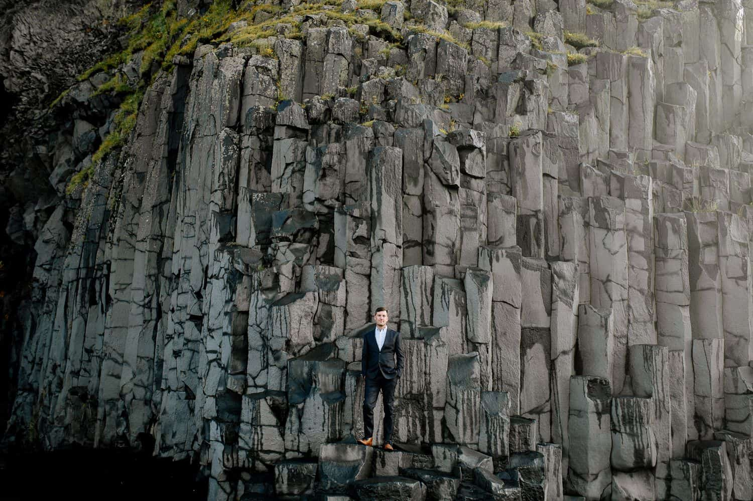 Man in a black suit and white shirt stands on a rock face in Iceland