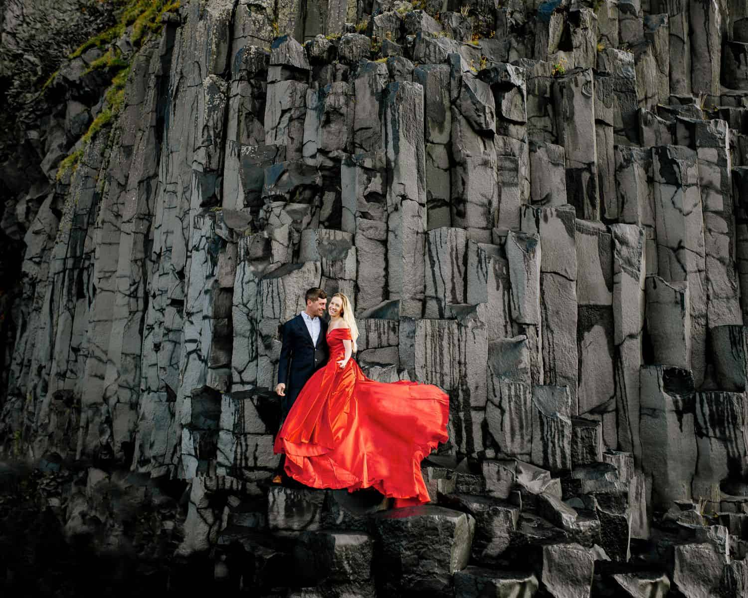 Man in a black suit and woman in a billowing red gown stand on a rock face in Iceland