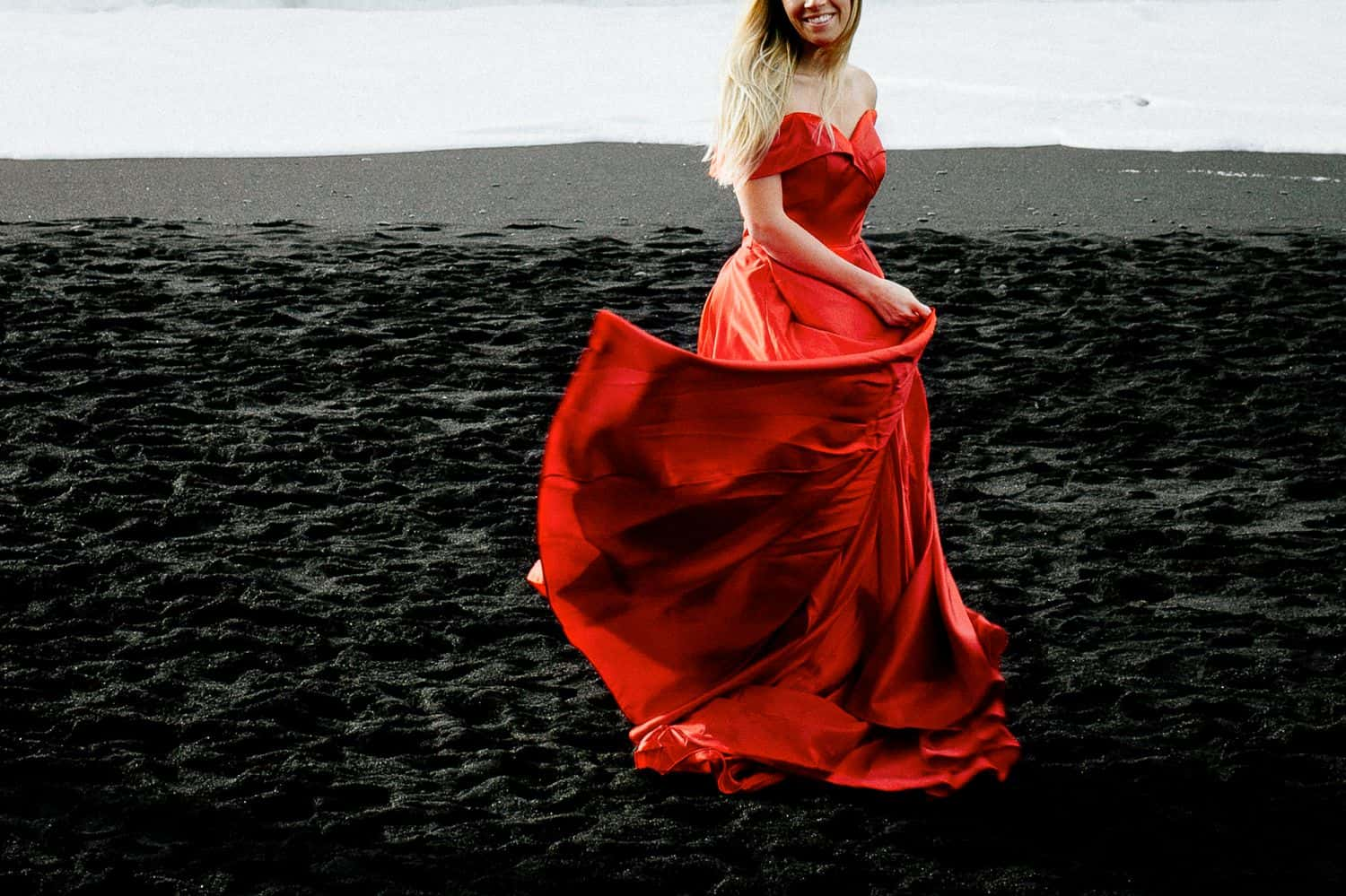 Woman in a flowing red dress dances on a black sand beach in Iceland. The photo is cropped so her eyes are not in the picture.