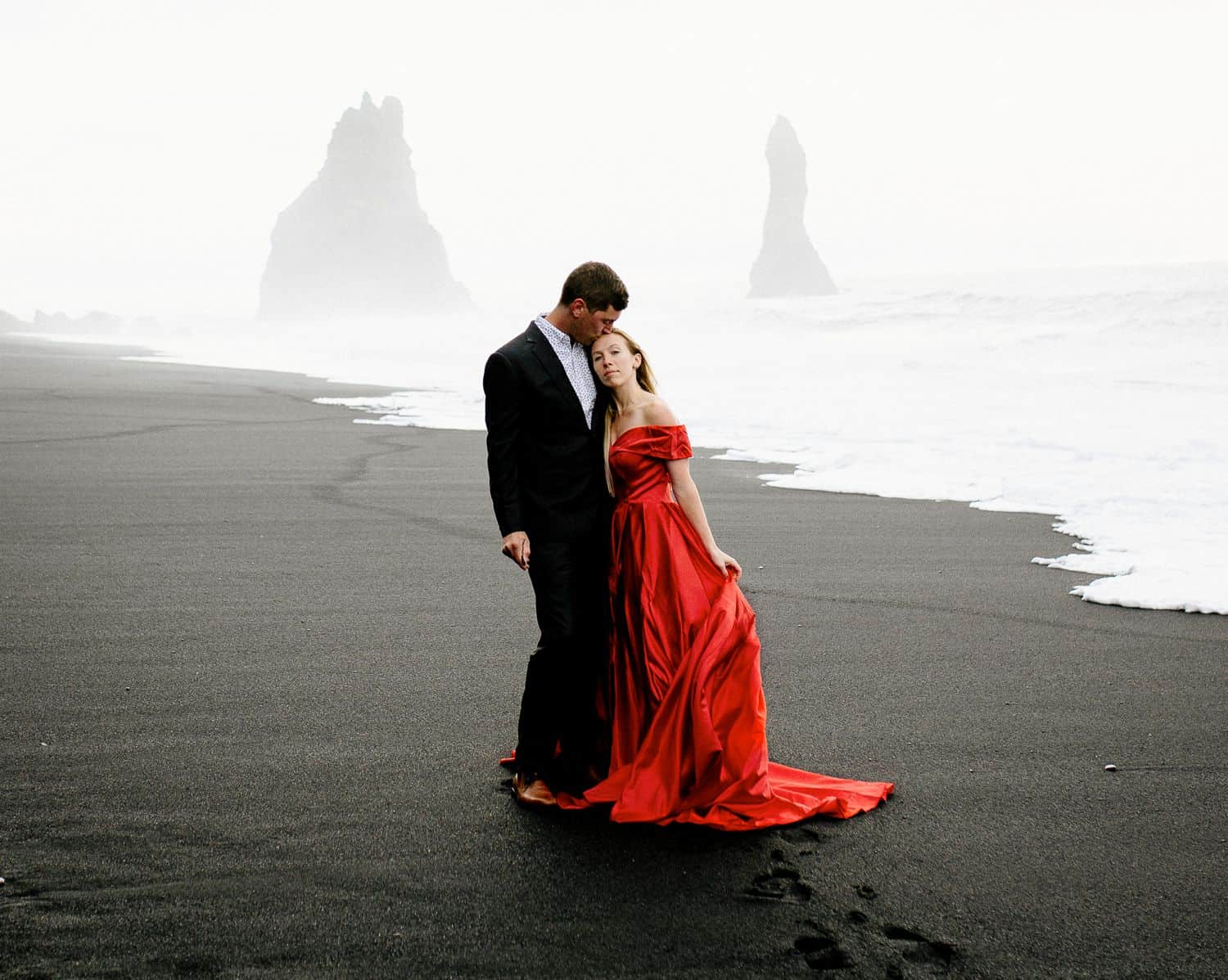 Man in a suit hugs a woman in a red dress on a black sand beach in iceland