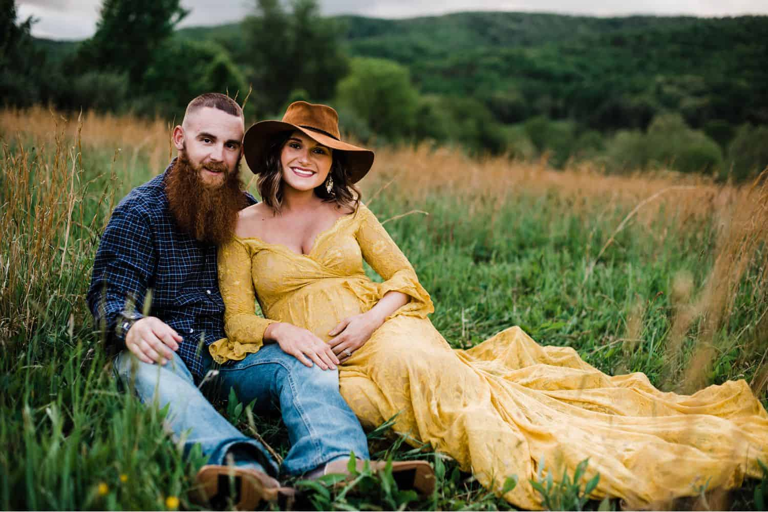 Maternity Poses: pregnant woman in a yellow dress and felt hat sits on the ground in a field with her husband who is wearing a plaid shirt