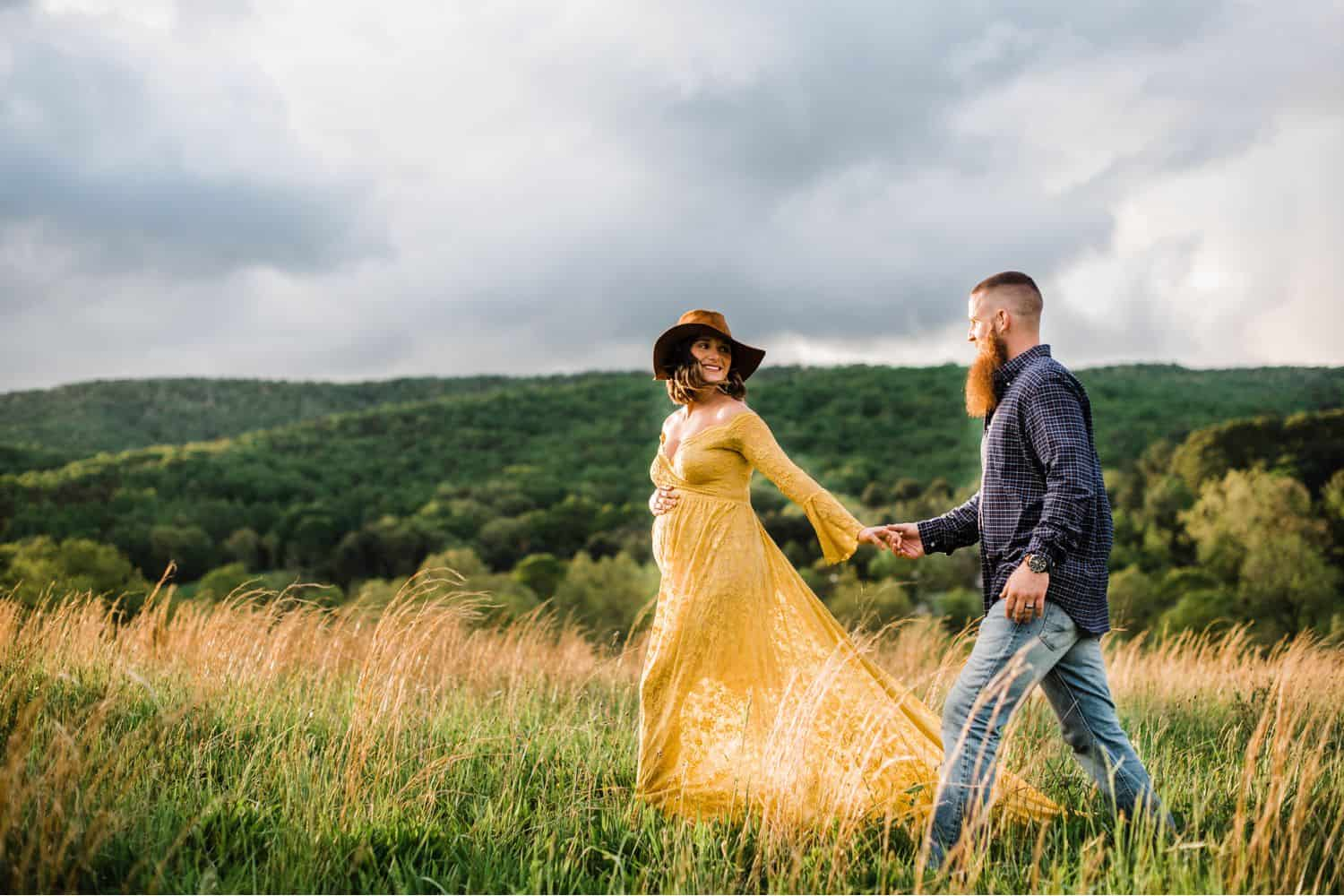 Maternity Poses: pregnant woman in a yellow dress leads a man in a plaid shirt through a field