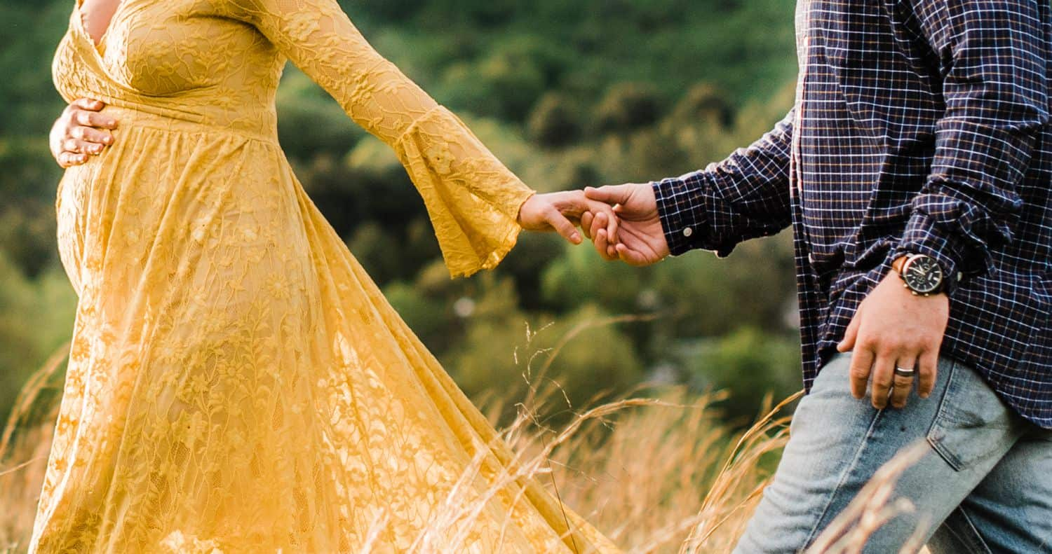 Maternity Poses: close-up photos shows pregnant woman in a yellow dress from the shoulders down, walking through a field leading her husband by the hand