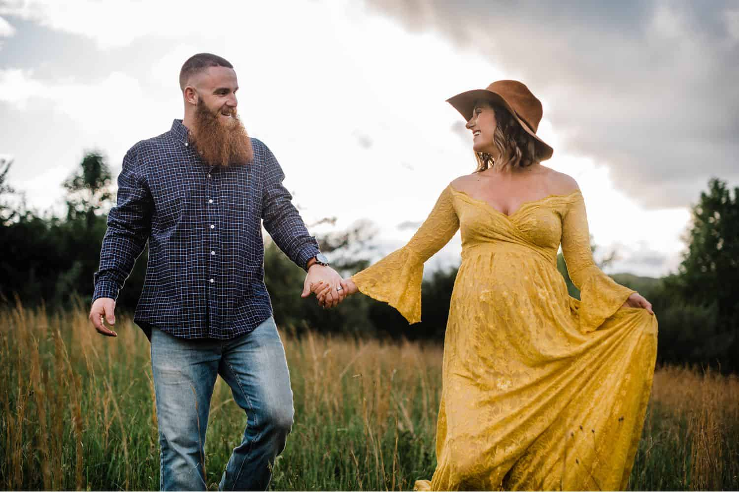Maternity Poses: man in a plaid shirt walks hand-in-hand with his pregnant wife who is wearing a yellow dress