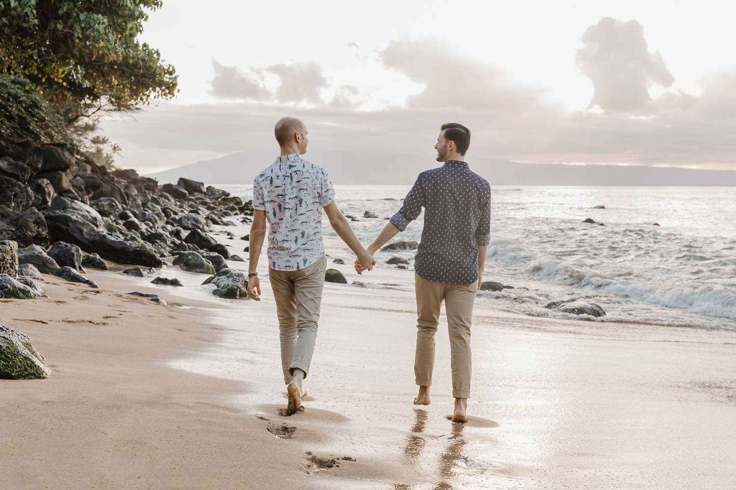 Two men stroll hand-in-hand on the beach at sunset.