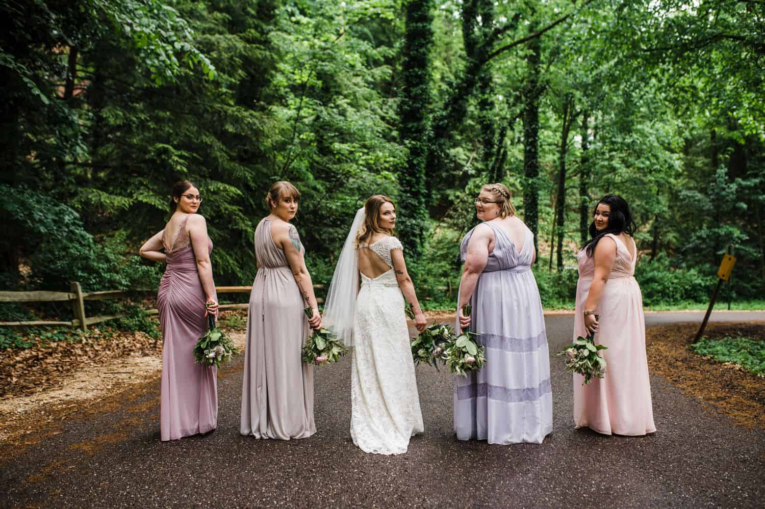 A bride and her bridesmaids post in the middle of a rural road and look over their shoulders.