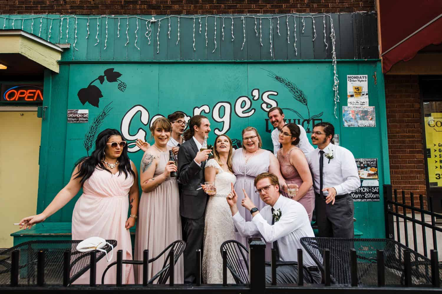 A wedding party does a silly pose in front of a turquoise restaurant wall.
