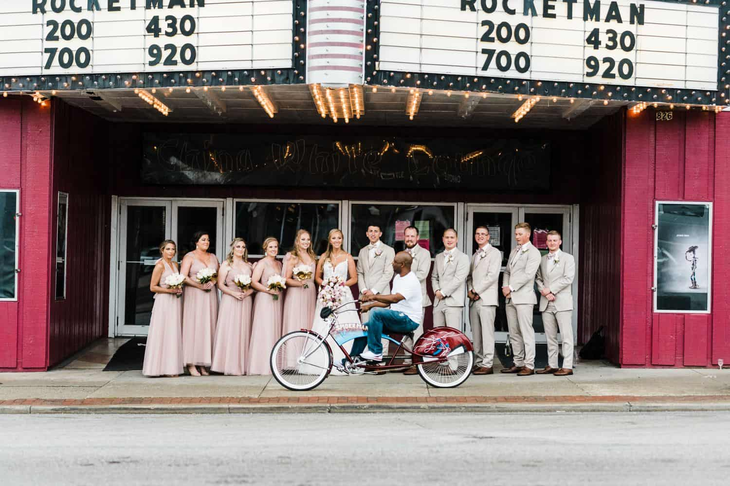 A wedding party poses beneath a theater marquee as a man rides by on his bike.