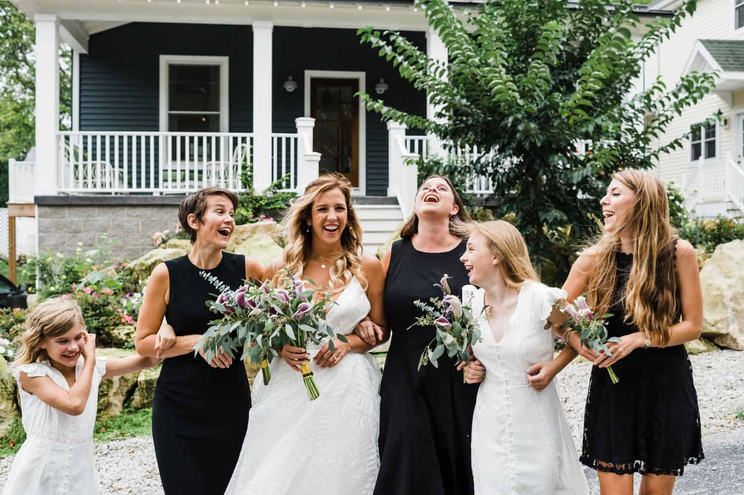 A bride and her bridesmaids walk arm in arm in front of an old farmhouse.