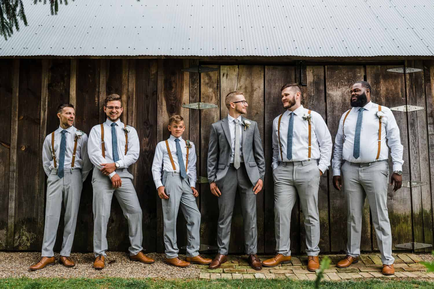 Groomsmen in shirts and suspenders stand casually in front of a barn wall.