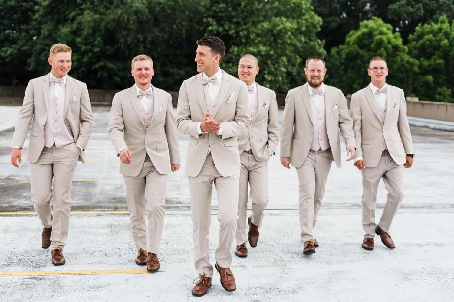 Groomsmen in tan suits walk casually across a tree-lined parking lot.