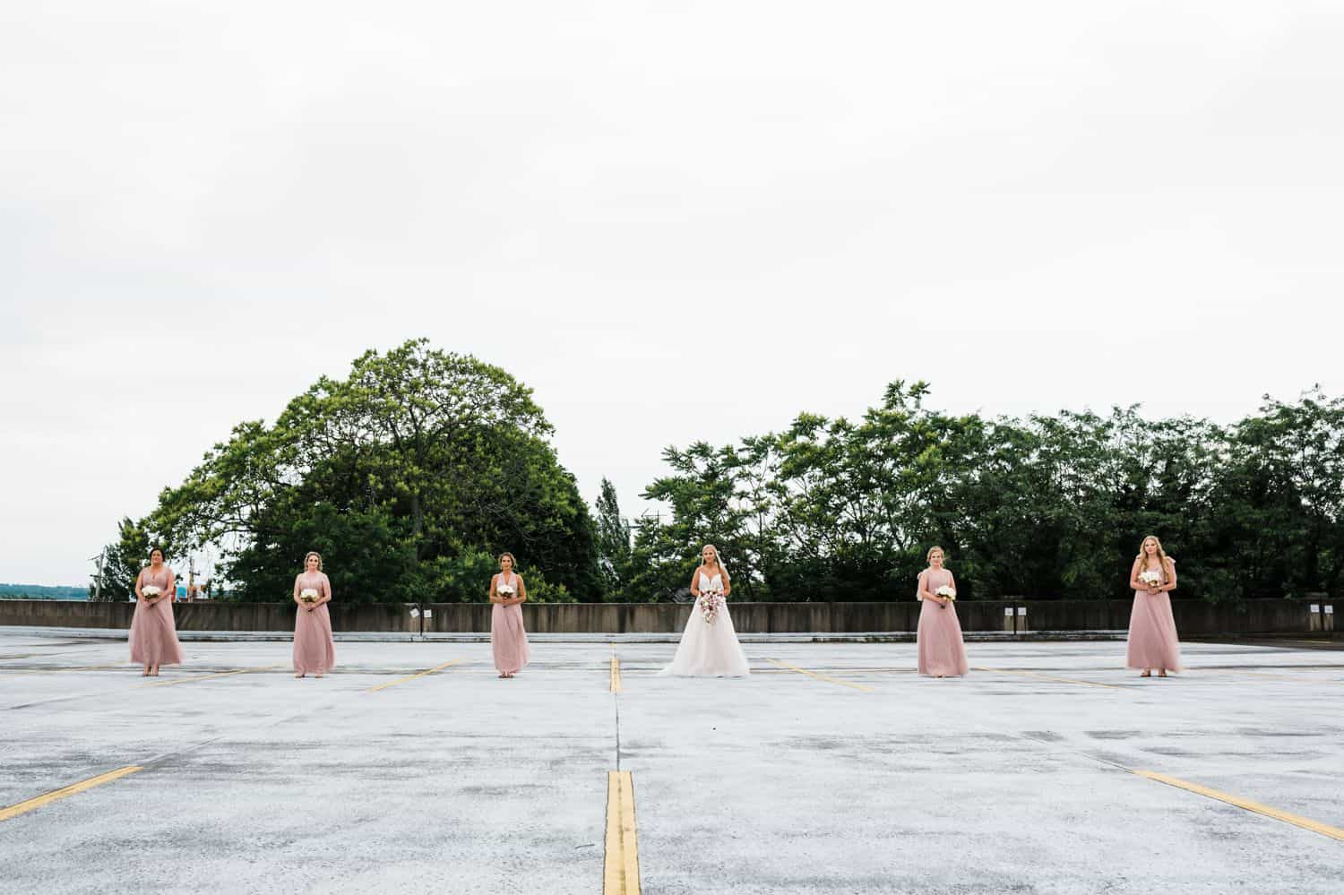 A bride and her bridesmaids stand in a widely-spaced line in a tree-lined parking lot.