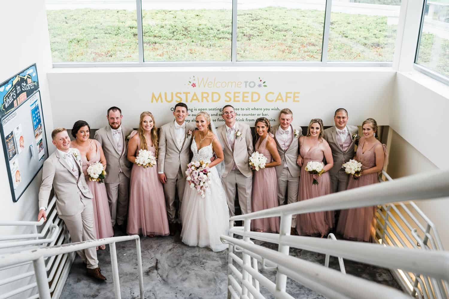A wedding party poses at the food of a staircase in a bright, naturally-lit studio space.