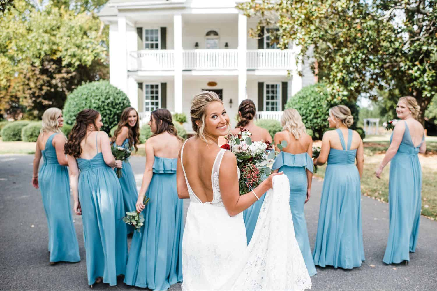 A bride looks back over her shoulder as her bridesmaids walk in front of her toward an antebellum mansion.
