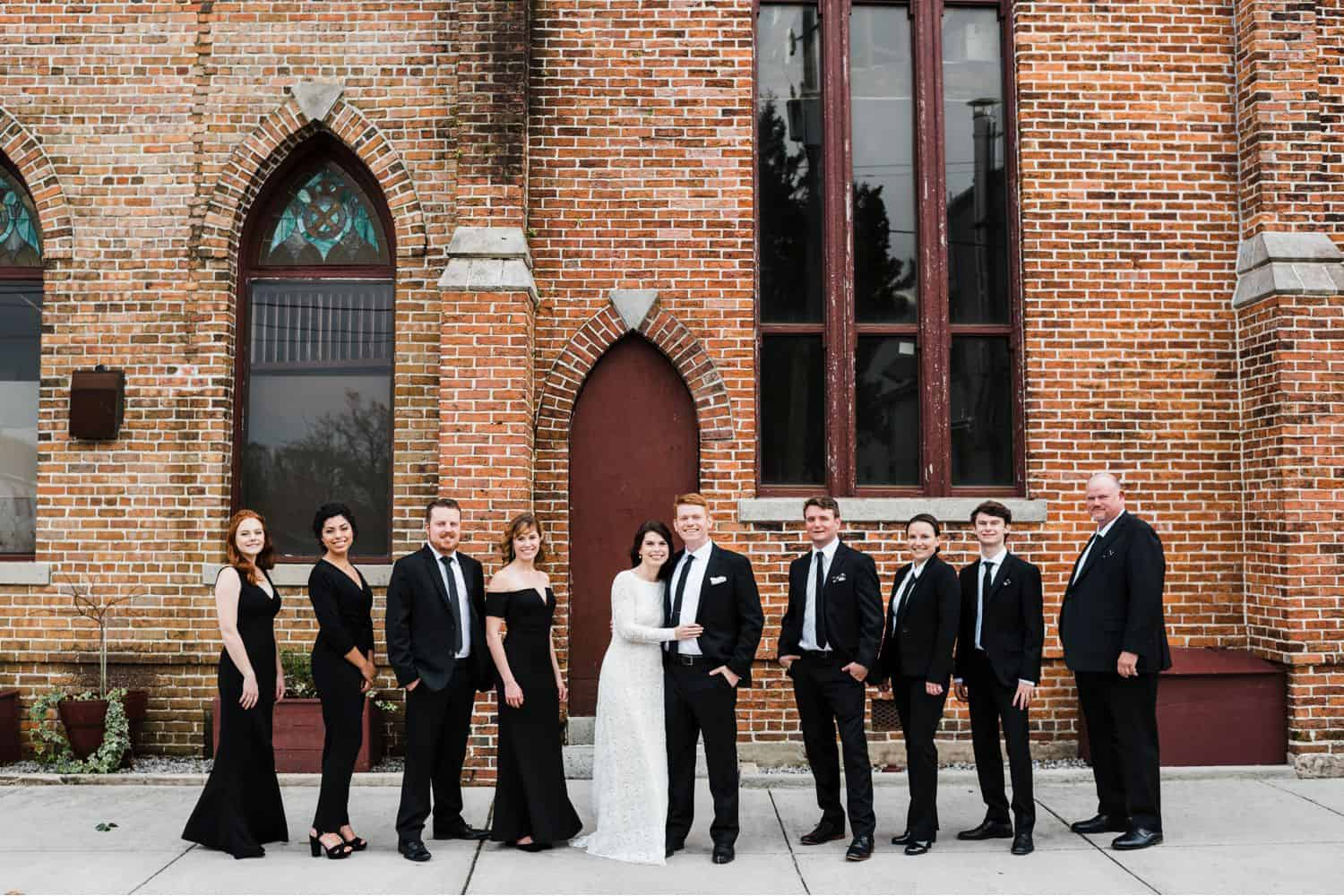 A wedding party dressed all in black poses before a brick cathedral.
