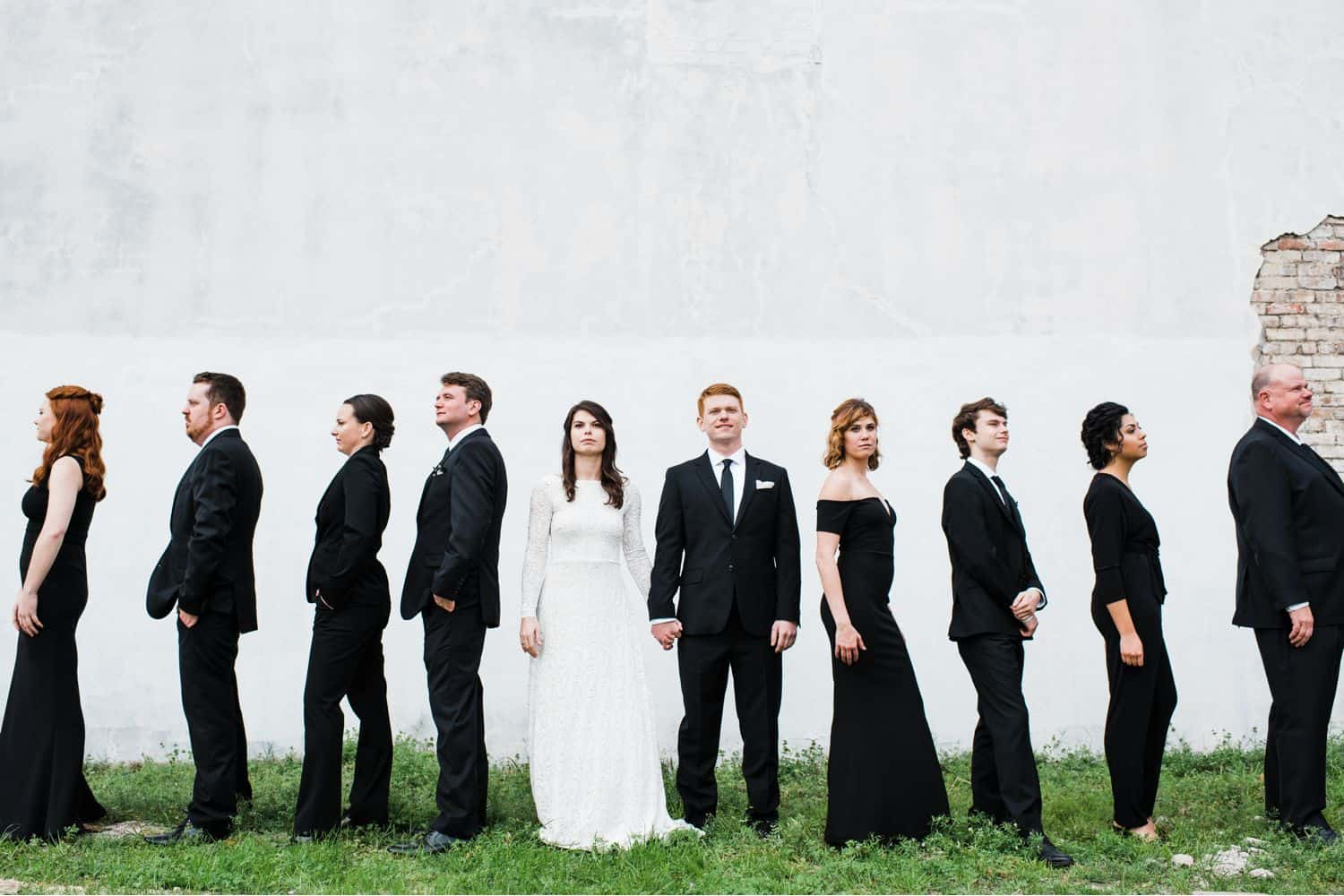 A wedding party stands side-by-side in front of a large white brick wall.