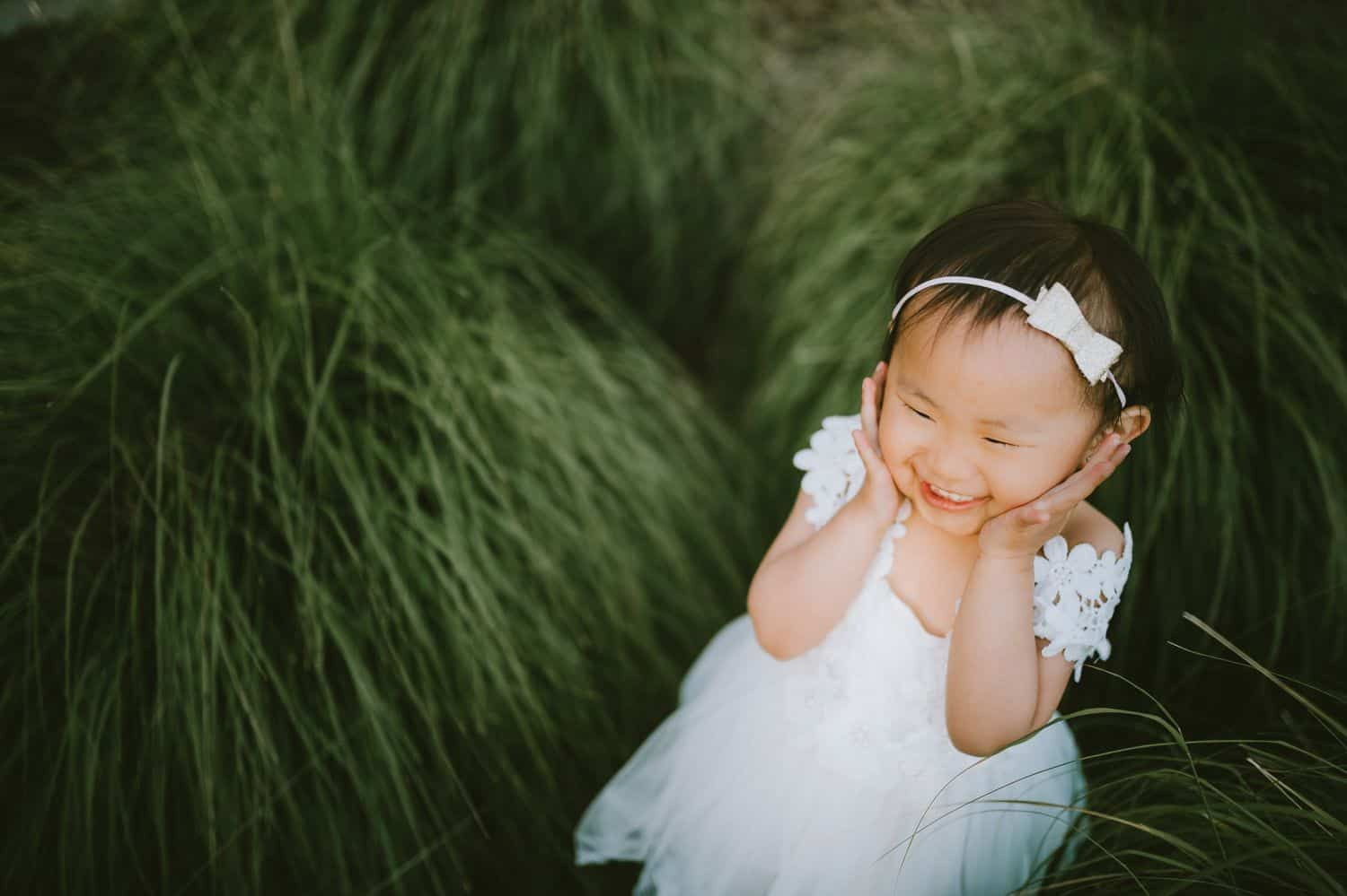 A little girl in a white dress and white headband stands in tall grass. She is laughing, and her hands are on either side of her face.