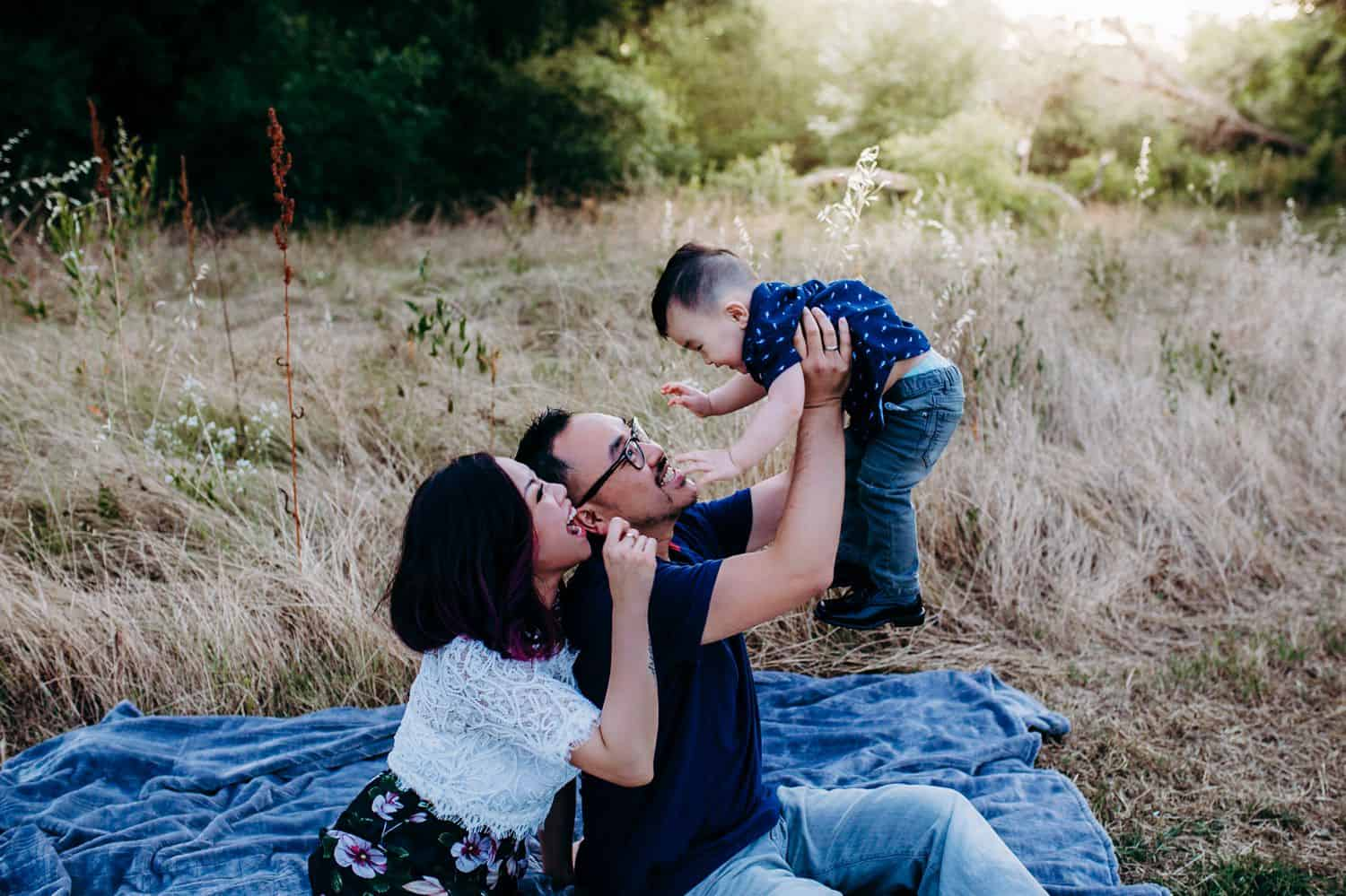 Two parents sit close together on a picnic blanket in the middle of a field while holding their toddler son up in the air and smiling.
